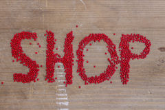 Shop. Written with red beads on a wooden surface Royalty Free Stock Image