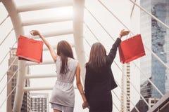 Shopaholic生活方式友谊妇女在购物中心中心的拿着购物带来 黑星期五和星期一网络销售概念 免版税库存照片