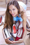 Shopaholic. Happy woman shopaholic with heap of shoes in shopping mall stock image