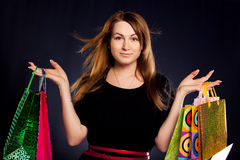 Shopaholic. Woman with shopping bags on black background royalty free stock image
