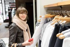 Shopaholic beautiful happy woman goes shopping in the city. The concept of shopping, sales and purchases of things. Shopaholic beautiful happy woman goes Royalty Free Stock Photography