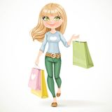 Shopaholic blond girl goes with paper bags Stock Image