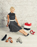 Young blonde woman in fashioned dress sitting in a chair in the store and choosing shoes (make shopping) Royalty Free Stock Photography