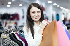 Shopaholic at clothing shop. Happy  shopaholic with shopping bags  at clothing shop Stock Photography