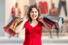 Shopaholic a excité les prises heureuses de femme beaucoup de sacs dans des mains image libre de droits