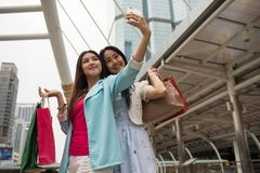Shopaholic female friends seflie in city. Beautiful Asian  shopaholic female friends selfie or take photo by smartphone  with modern Bangkok city background Royalty Free Stock Photos