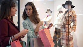 Shopaholic flickvänner med påsar som nära står, shoppar fönstret med den nya samlingen av kläder och diskuterar köp i galleria arkivfilmer