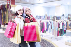 Shopaholic friends holding bags in the mall Stock Photo