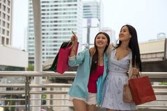 Shopaholic friends shopping in city. Happy Asian female shopaholic friends look for shopping mall in urban town. Two women enjoying summer discount sale at stock photography