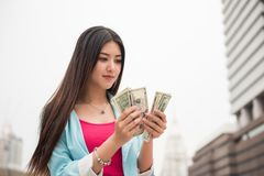 Shopaholic girl count money for shopping. Happy shopaholic Asian girl counting dollar bills for shopping at modern city with copy space for text. Discount or Stock Image