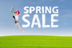 Shopaholic jumps with spring sale sign Royalty Free Stock Photo