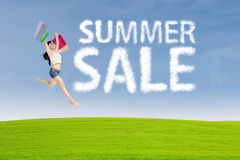 Shopaholic jumps with summer sale sign Stock Photos