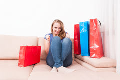 Shopaholic lady sitting on couch acting happy Royalty Free Stock Photo