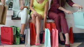 Shopaholic-Mädchen passen die Neuanschaffungen auf, die von den Rabatten und von den Verkäufen und von den hellen Einkaufstaschen stock video footage
