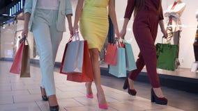 Shopaholic przyjaciele z papierowymi torbami w kolorowych ubraniach na heeled chodzący pobliskim przechują w centrum handlowym, t zdjęcie wideo
