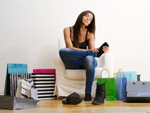 Shopaholic rubbing her tired feet. Photo of a young beautiful female sitting on a chair surrounded by shopping bags and rubbing her sore feet Royalty Free Stock Photography