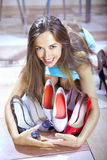 Shopaholic with shoes. Happy woman shopaholic with heap of shoes in shopping mall stock photos