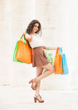 Shopaholic. Shopping love. Beautiful happy woman with bags. A happy and smiling woman just went shopping. Beautiful smile. Colored bags in hand. Long curly hair Stock Photography