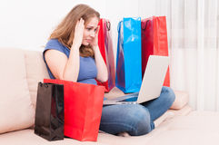 Shopaholic sitting on couch holding her head Stock Photography