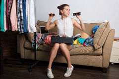 Shopaholic woman and her wardrobe. Young hipster woman sorting her wardrobe Royalty Free Stock Photo