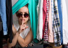 Shopaholic woman and her wardrobe. Young hipster woman sorting her wardrobe Stock Photos