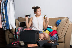 Shopaholic woman and her wardrobe. Young hipster woman sorting her wardrobe Royalty Free Stock Photography