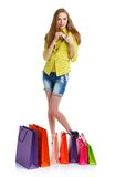 Shopaholic woman with shopping bags and credit card over white b Stock Photography