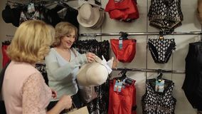 Shopaholic woman trying elegant hat on in store stock video footage