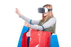 Shopaholic woman using virtual reality equipment. And holding shopping bags on white background Royalty Free Stock Image