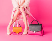 Shopaholic woman with woman`s handbags on a pink background Royalty Free Stock Photo