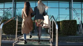 Shopaholic women coming in the store for shopping. Back view of two attractive young women with shopping bags going to the store for shopping. Beautiful girl stock video footage