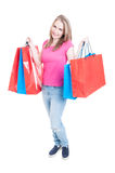 Shopaholic young girl holding shopping bags in both hands Stock Photography