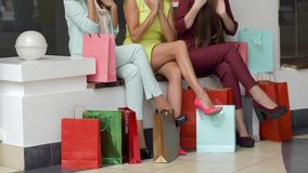 Shopaholics女性考虑的购买到在腿附近的纸袋里在参观在季节期间的时兴的精品店以后  股票视频