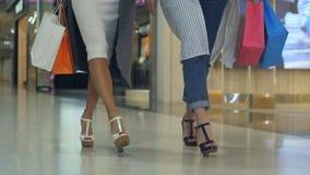 shopaholics的腿与步行沿着向下购物中心的购物袋的 库存照片