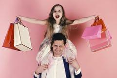 Shopaholics, παιδική ηλικία και οικογενειακή έννοια Κορίτσι και άτομο με τις εύθυμες τσάντες αγορών λαβής προσώπων Στοκ Εικόνες