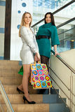Shopaholics. Two beautiful woman stands on stairs in big shop. Holding bags. Whole body stock photography