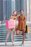 Shopaholics auf Käufen Zwei schöne Freundinnen in Kleidern h Stockfotografie