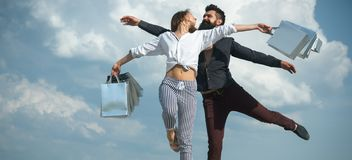 Shopaholics being addicted to shopping. Shopaholic couple. Happy couple of shopaholics enjoy doing shopping together. Bearded men and sexy fashion women stock image