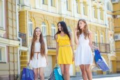 Shopaholics de trois amies Filles tenant des paniers et W Images libres de droits