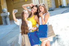 Shopaholics do selfie on a cell phone. Girls holding shopping ba Stock Images
