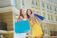 Shopaholics girlfriends laugh. Two girlfriends holding shopping Royalty Free Stock Photo