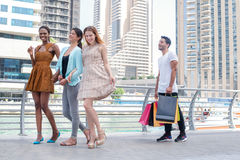 Shopaholics girls go with purchases. Beautiful girls in dresses Royalty Free Stock Photography