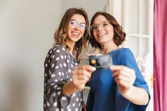 Shopaholics heureux de jeunes femmes montrant la carte de crédit Image stock