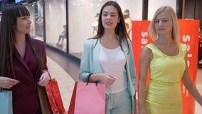 Shopaholics op aankopen, vrouwenvrienden in modieuze levendige kleren gaat voorbij vensters van manieropslag in seizoen van stock video