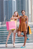 Shopaholics on purchases. Two beautiful girlfriends in dresses h Stock Photography