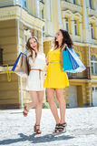 Shopaholics for a walk. Two girlfriends holding shopping bags an Royalty Free Stock Photography