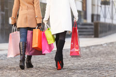 Shopaholics at work. Rear view of two women walking with shoppin Stock Images