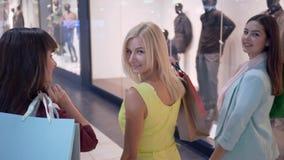 Shopaholism, amigos da mulher dos clientes anda através da alameda durante a compra no boutique da forma na estação dos discontos vídeos de arquivo