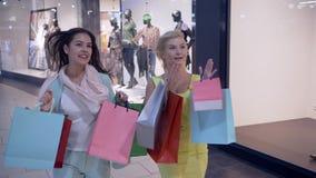 Shopaholism, amigos femeninos hermosos que corren a través de centro comercial en a las tiendas durante viernes negro, texto apar metrajes