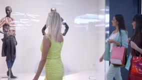 Shopaholism, las muchachas sonrientes de los clientes ve ventanas de moda de la tienda con los maniquíes de temporada de descuent metrajes